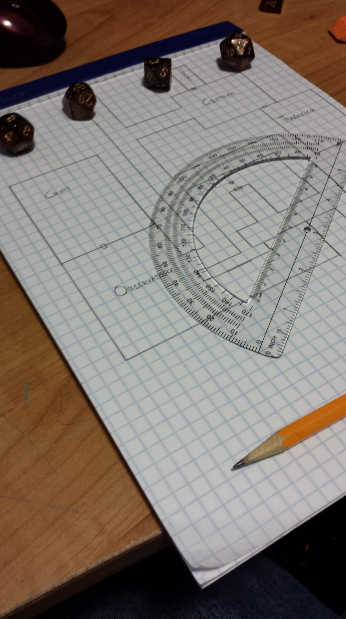 Hand-drawn map on graph paper with dice, pencil, and protractor