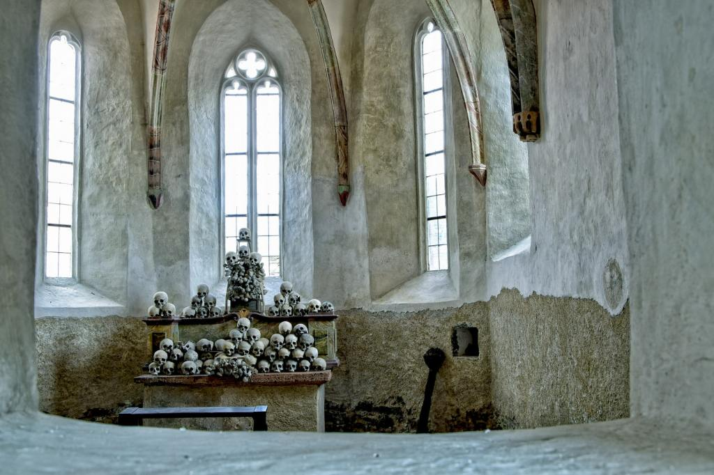 A pile of skulls in a a concrete room with high arched windows.