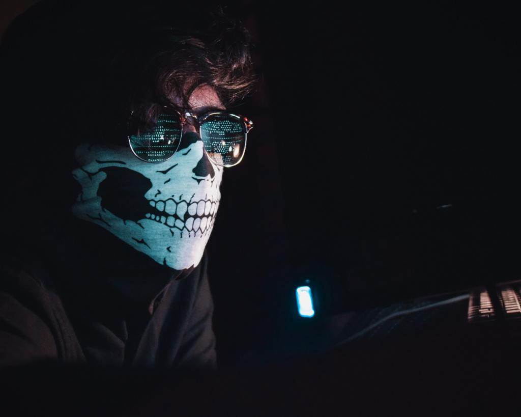 Someone is looking at a computer while their glasses reflect the text on the screen. The lower half of their face is covered in a skull maskk.