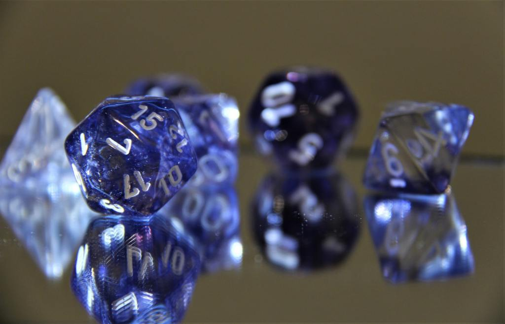 Crystal blue polyhedral dice on a reflective surface