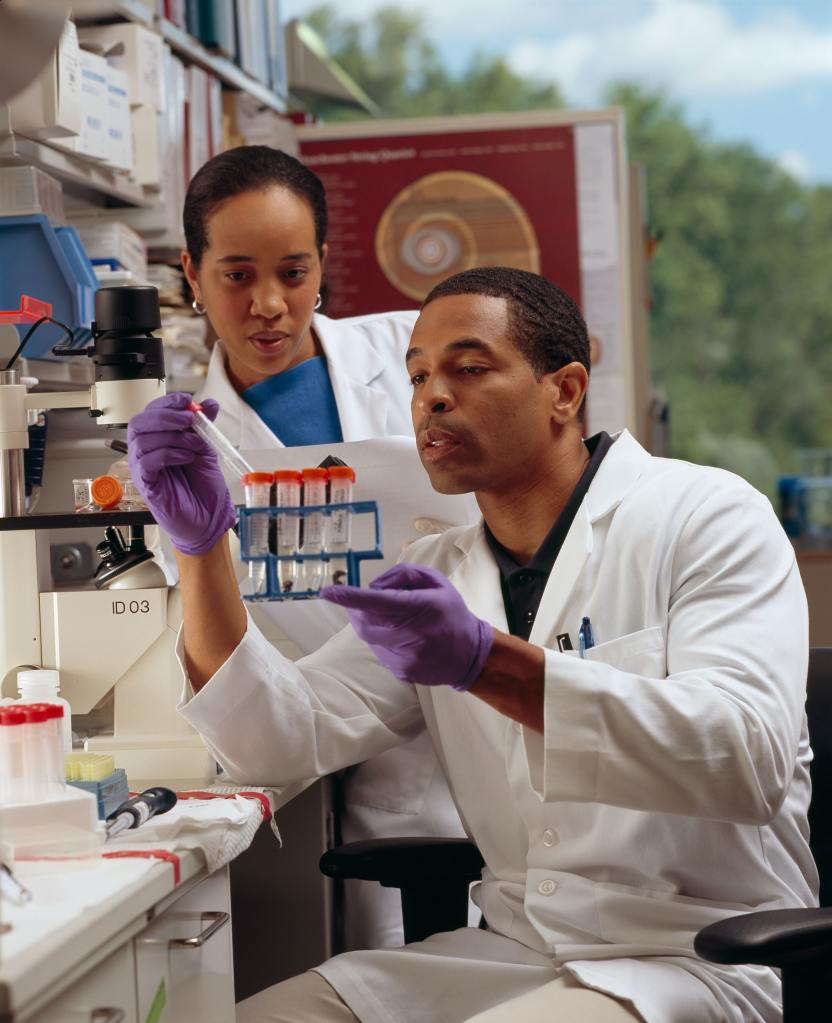 A Black male researcher checks test tubes as a Black female cancer researcher looks on.