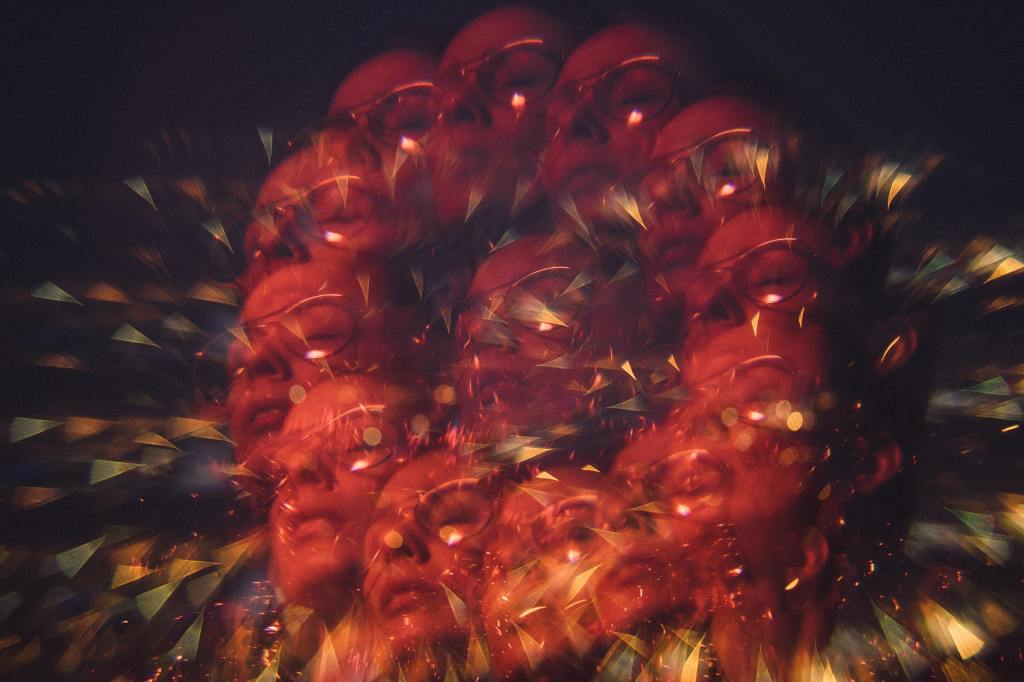 Multiple exposures of a woman illuminated by red light with her eyes closed