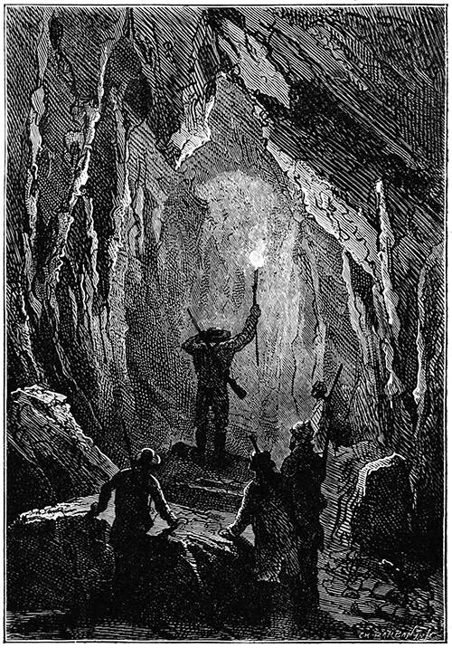 A group of men stands at the entrance of a rocky tunnel. One of them has climbed onto a large rock lying on the ground and holds a torch high above his head, peering into the depths ahead of him.