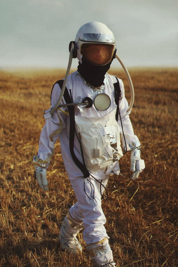 Man in white long sleeve shirt and white pants with technical gear hanging and fogged helmet walking through a field