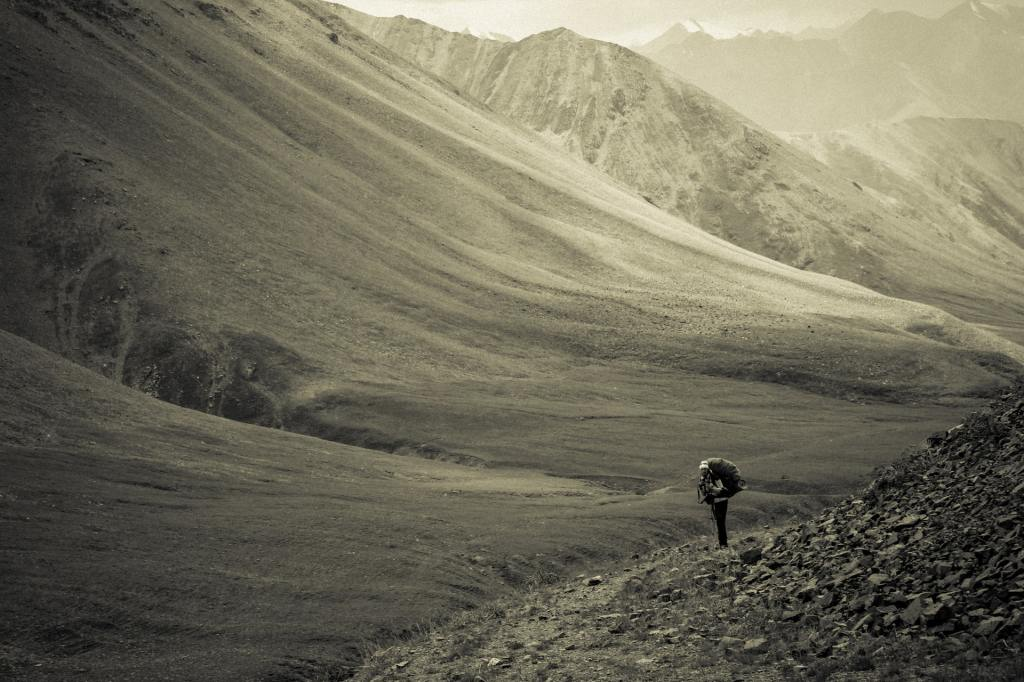 grayscale photo of person walking on mountain feet during daytime in Kyrgyzstan