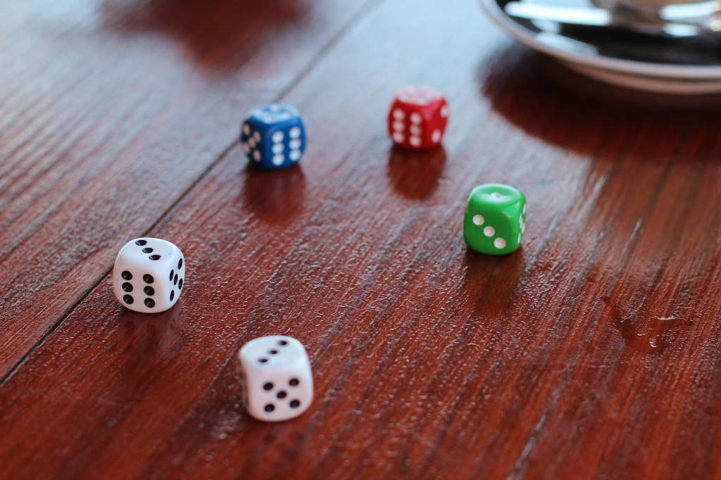 Five assorted color dice on a wooden tabletop