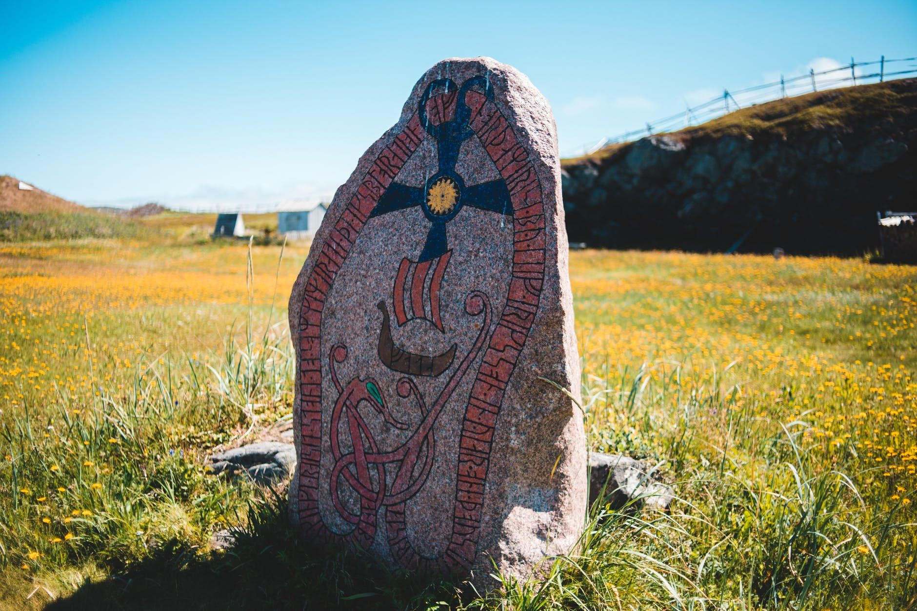 An ancient runestone stands in a meadow surrounded by flowers