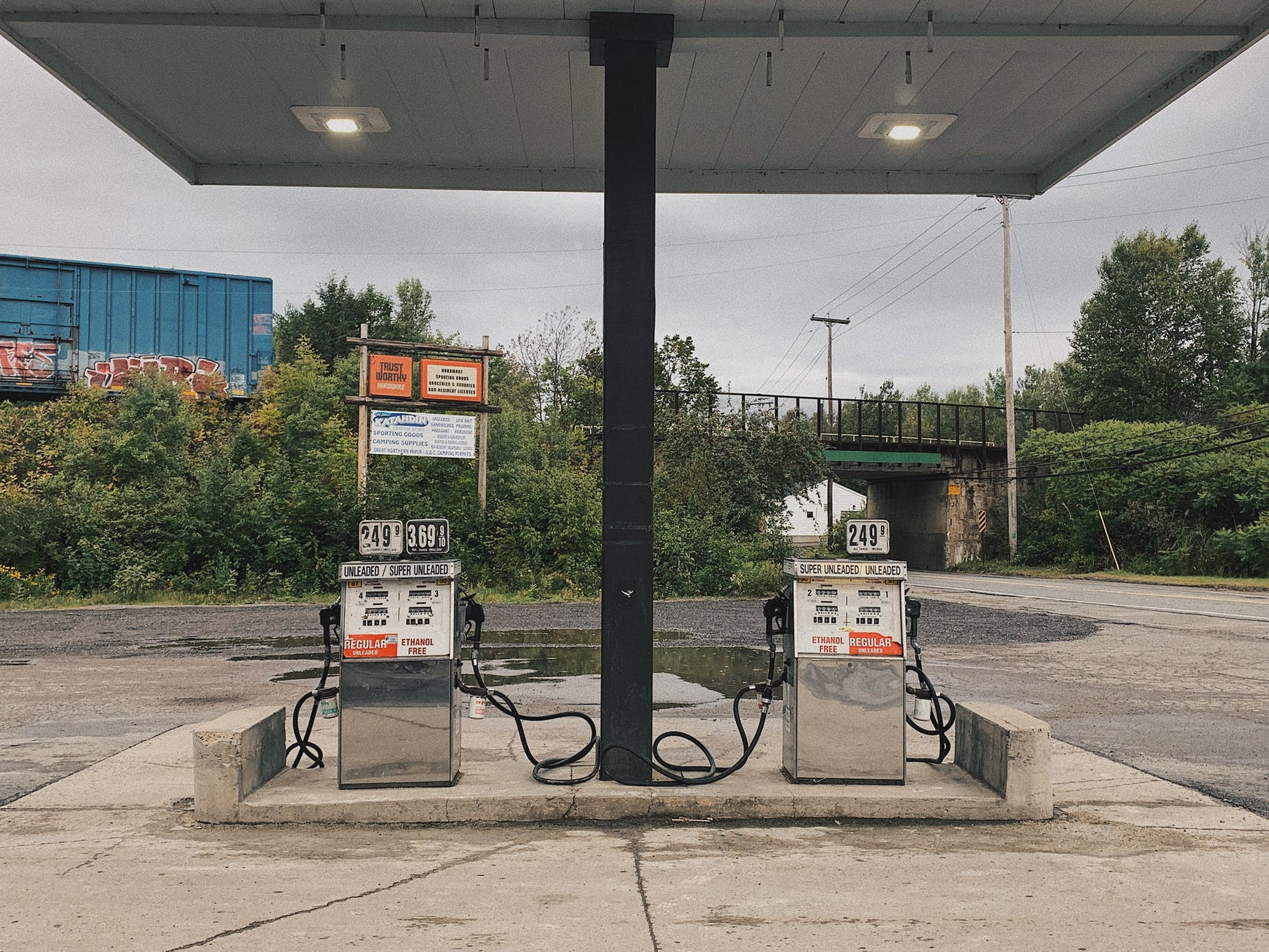 An old abandoned gas station with a railroad in the background.