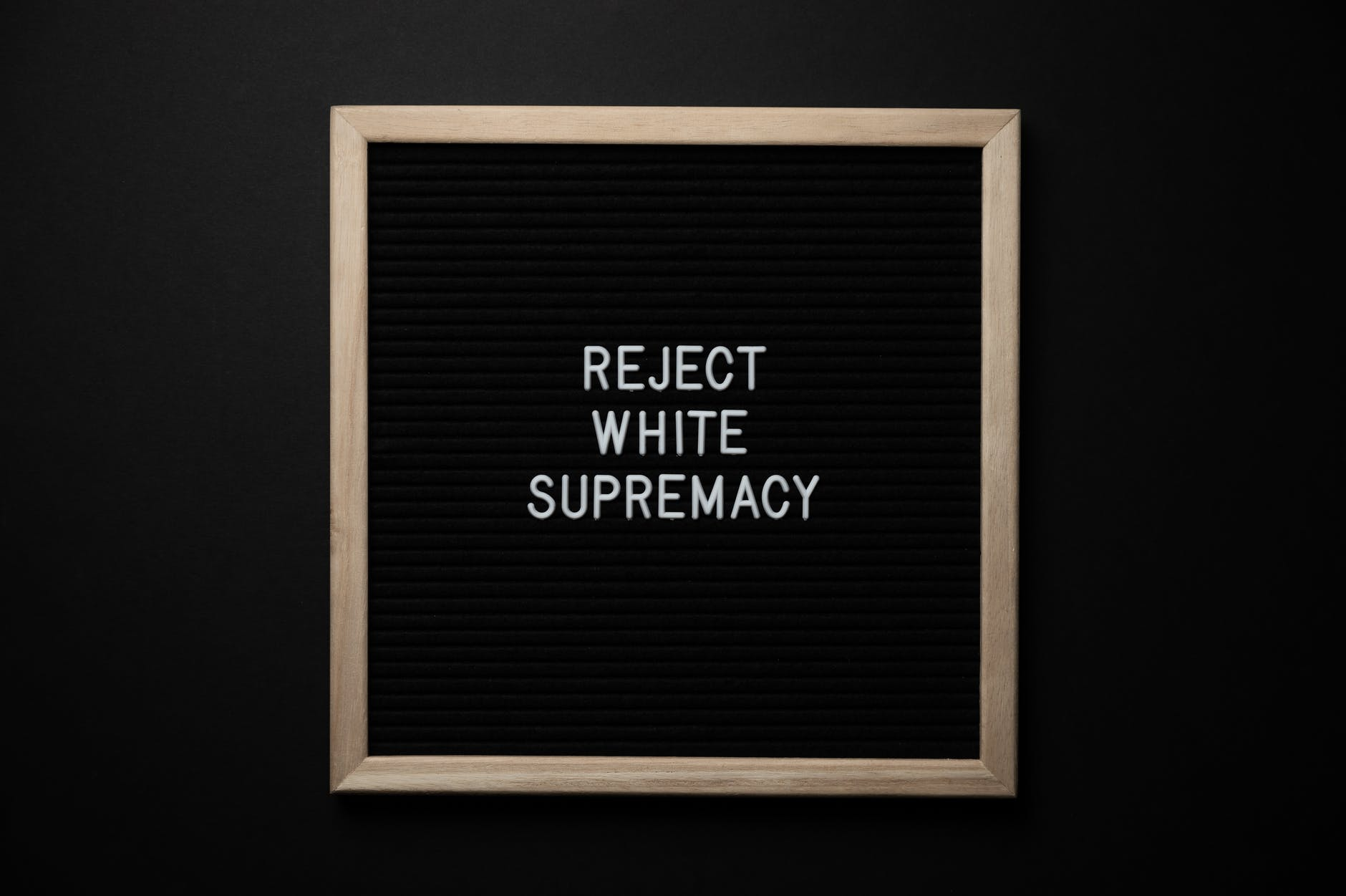 """A sign with the words """"REJECT WHITE SUPREMACY"""""""