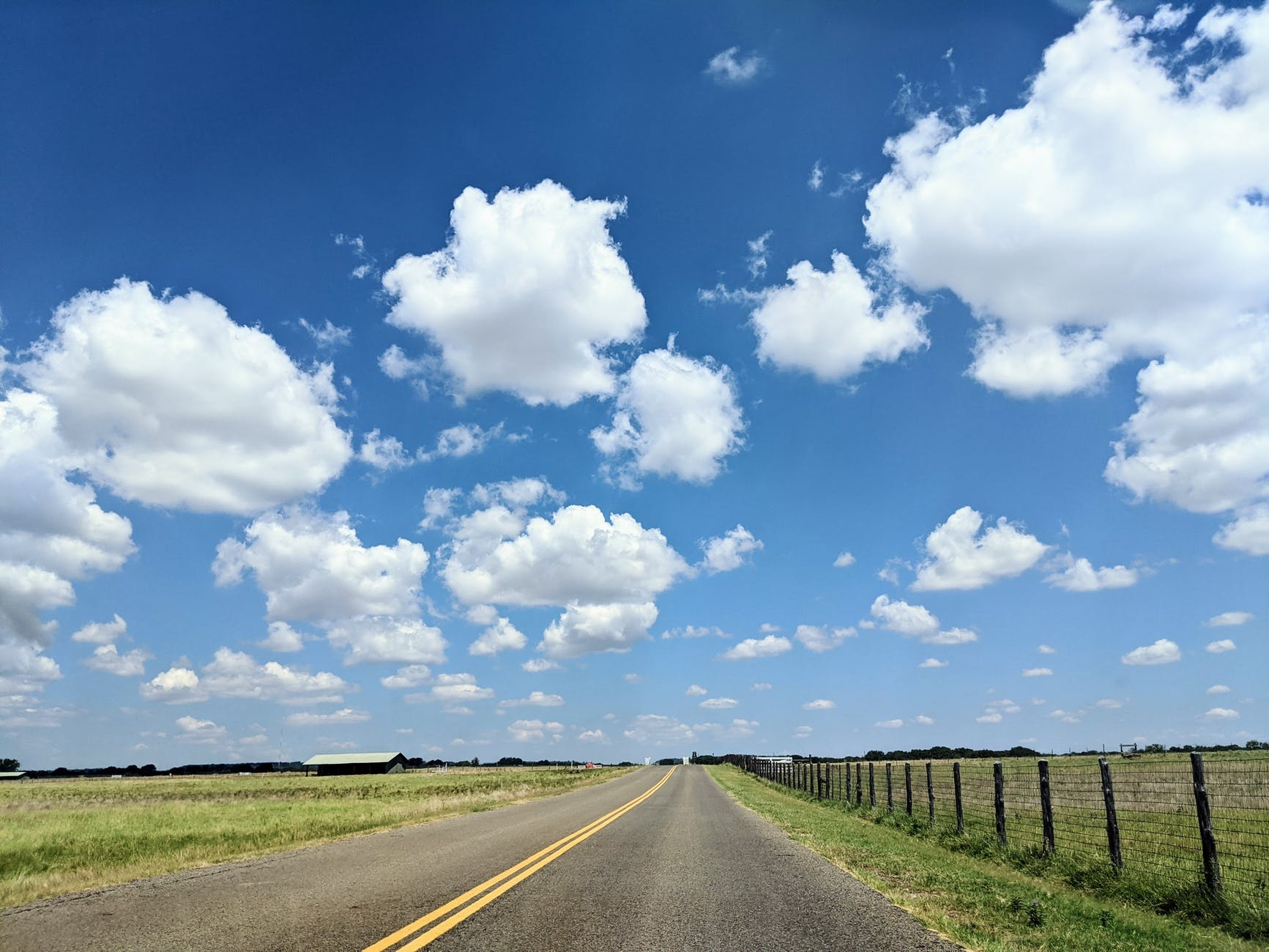 A highway somewhere on the Texas plains with a blue sky and a few clouds.
